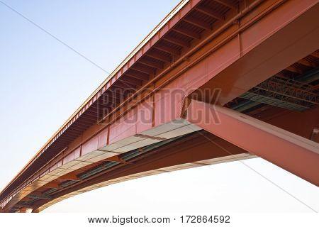 Under red bridge construction over blue sky
