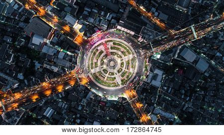 Road roundabout with car lots Wongwian Yai in BangkokThailand. street large beautiful downtown at night light. Aerial view Top view cityscape Rush hour traffic jam