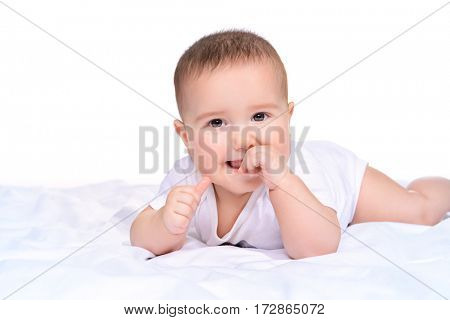 Cute little baby lying on the blanket and smiling. Baby healthcare. Family concept. Isolated over white.