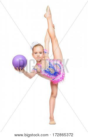 Beautiful little gymnast girl doing gymnastics with a ball. Professional sports. Isolated over white. Copy space.