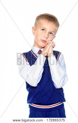 Nine year old boy in elegant formal suit looking dreamily. Educational concept. Isolated over white background.