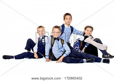 Portrait of happy school friends posing together at studio. School uniform. Education. Isolated over white.