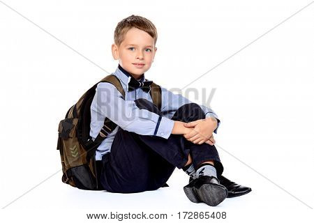 Full length portrait of a cute smiling nine year old boy in a school uniform and school bag. Educational concept. Children's fashion. Isolated over white background. Copy space.