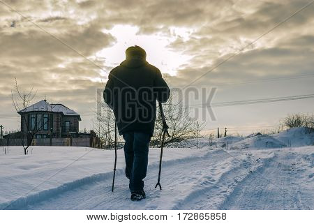 Film toned image with lonely wanderer on a snowy road