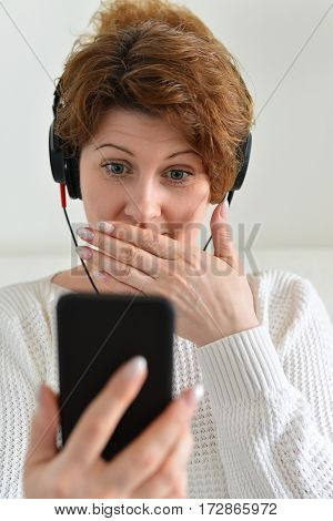 Woman in a headphones with surprise looks at smartphone