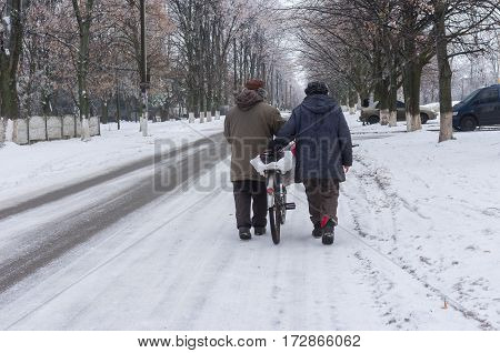 DNEPR UKRAINE - JANUARY 02 2017: Elderly pair walking on a winter street rolling old bicycle loaded with bags in Dnepr city Ukraine at January 02,2017