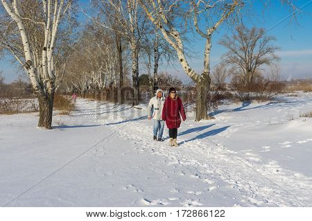 DNEPR UKRAINE - JANUARY 08 2017: People walking in winter park at sunny weekend in Dnepr city Ukraine at January 08, 2017