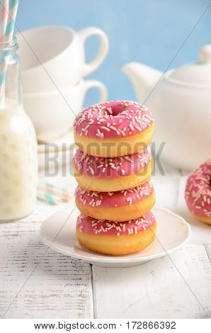 Baked donuts with pink glaze and sprinkles, selective focus