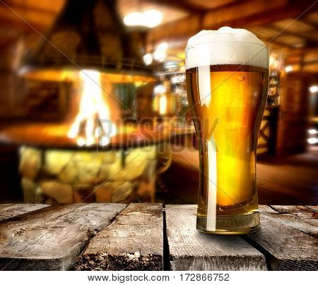 Beer on wooden table in bar with furnace