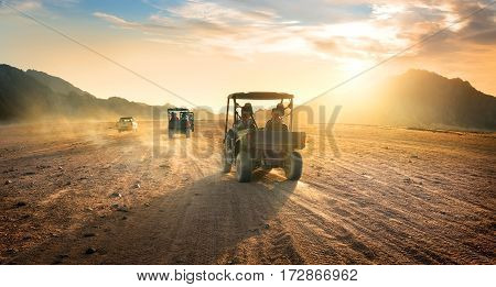 Buggies in sand desert at the sunset