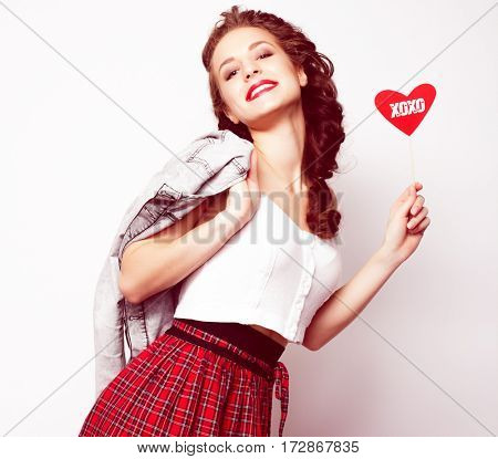 Party image. Playful young woman holding a party heart.Special fashionable toning.