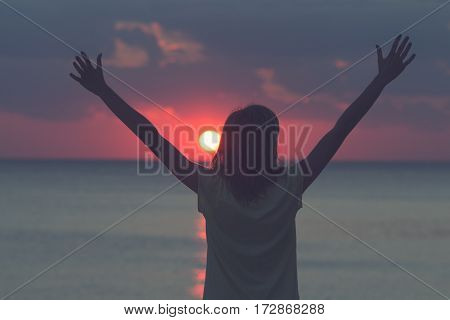 Silhouette of a girl enjoying the sunset / sunrise with arms wide open.