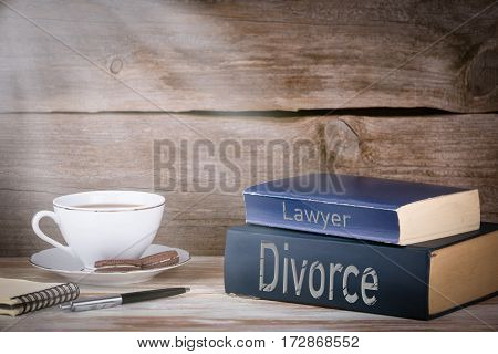 Divorce and Lawyer. Stack of books on wooden desk.