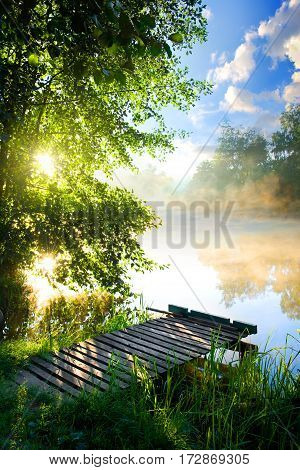 Fishing pier on river in the morning