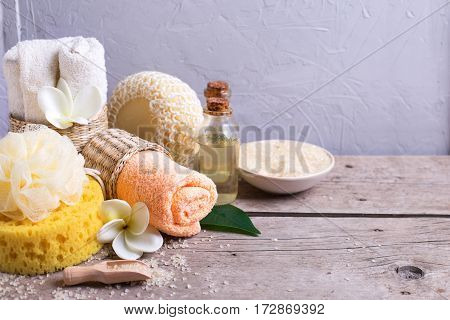 Spa composition. Sea salt towels bottle with aroma oil and wisps on wooden background. Selective focus. Copy space.