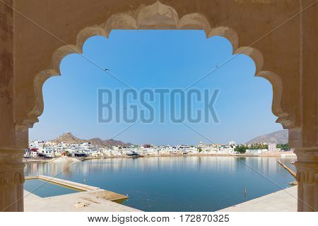 Framed View From Archway At Pushkar, Rajasthan, India. Temples, Buildings And Ghats On The Holy Wate