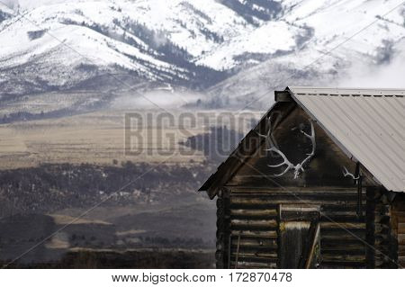 Old cabin with snow covered mountains in background and elk antlers