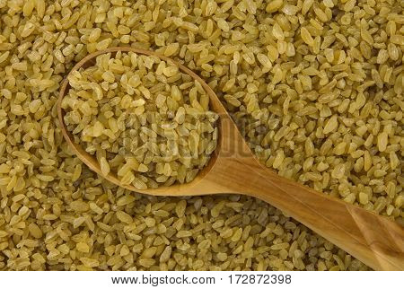 background of dry bulgur wheat with spoon from above