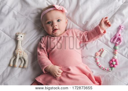 Top view of cute baby girl in pink dress looking at camera and smiling while lying on bed