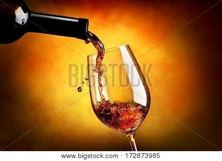 Wine pouring in wineglass on an orange background.