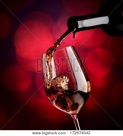 Red wine pouring in wineglass on a vinous bokeh background.
