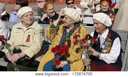 NOVOURALSK/ RUSSIA - MAY 9. Old women - veterans of the great Patriotic War with medals and bouquets of carnations on May 9, 2012 in city Novouralsk, Sverdlovsk region, Russia.