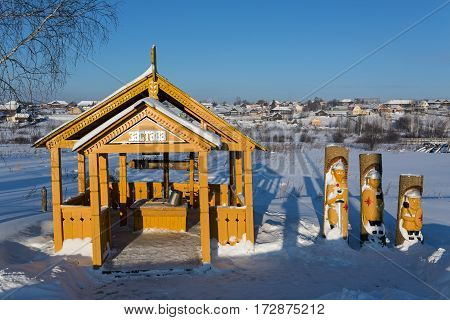 VISIM/ RUSSIA - JANUARY 8. Wooden well and statues of the three Russian heroes in the old believer village Visim on January 8, 2015. Russia.