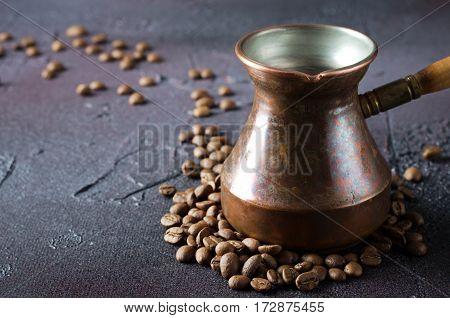 Old copper coffee pot and coffee beans on dark rustic background, horizontal