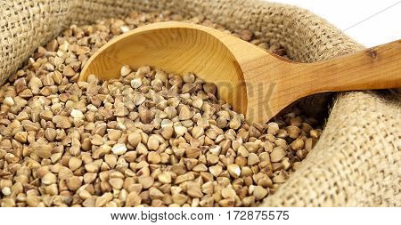 Buckwheat with wooden spoon in jute sack close up
