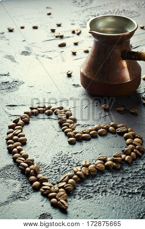 Old copper coffee pot and coffee beans in heart shape on dark rustic background. Vertical