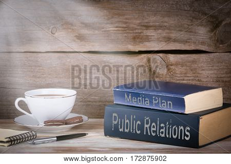Public Relations and Media Plan. Stack of books on wooden desk.