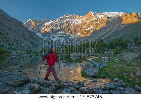 Woman with sticks crossing stream. Fann Mountains. Kulikalon lakes tableland.