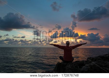 Woman sits as yogi with outstretched hands and contemplates beautiful sunset over sea.