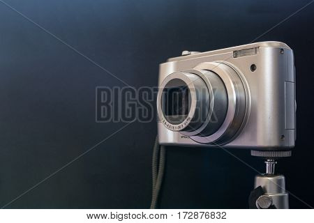 Silver compact digital photo camera. Side view.