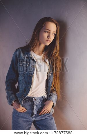 Conceived Schoolgirl. Closeup fashion studio portrait of hipster young tender woman in denim vest over against grunge wall background. Caucasian teen woman model posing indoors and looking away