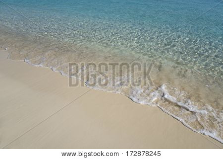 Water edge. Wat sand and transparent tranquil sea.