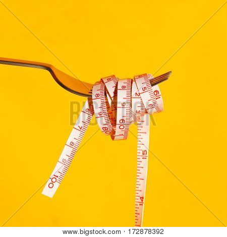 Fork with measuring tape on yellow background