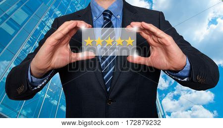 Businessman holding five star rating. Modern business skyscrapers background. Business technology internet concept. Stock Photo