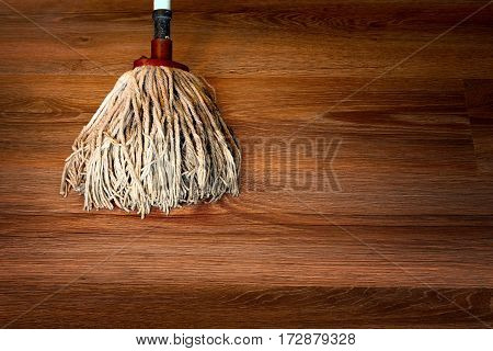 close up of cleaning brown wooden parquet with a mop