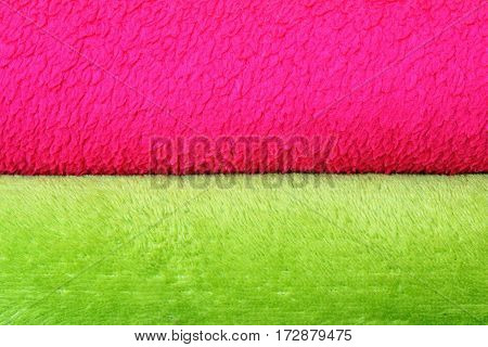 colorful background of textured blankets detail of stack with green and pink material