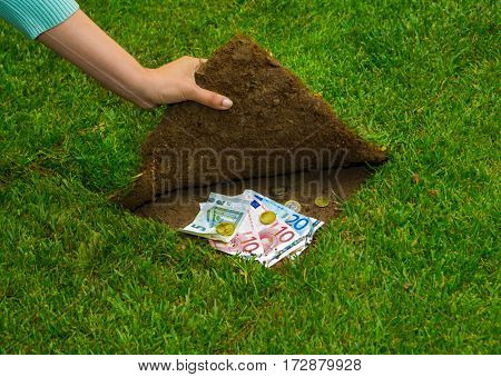 Finances concept, hands hiding money under the grass