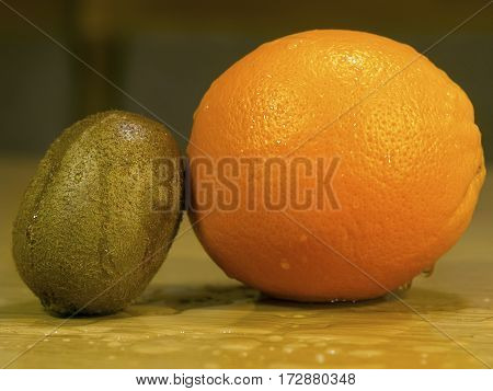 The orange and kiwi on a wooden wet surface closeup