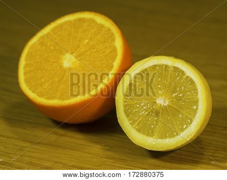 The cut orange and lemon on a wooden surface