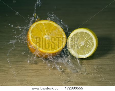 The orange and lemon on wooden surface with waterdrops