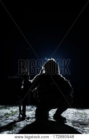 Army sniper with big rifle sitting holding rifle on black background. Lone killer in the moonlight