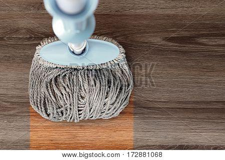 washing dirty wood floor with big mop