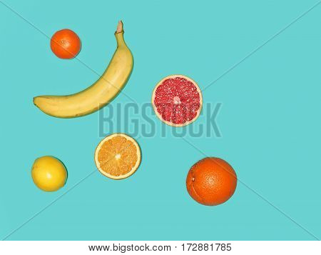 The group of fresh banana and fresh fruits against the blue background