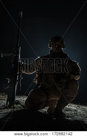 Army sniper with big rifle sitting holding rifle on black background