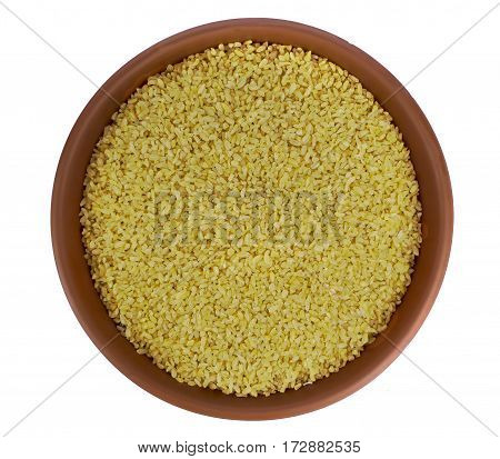 Dry bulgur wheat in a clay bowl isolated on white