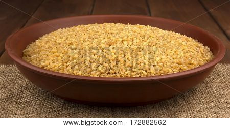 Dry bulgur wheat in a clay bowl on the sacking